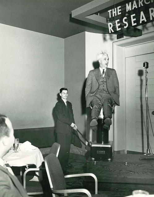 """西屋员工理查德·希区柯克博士坐在便携式范德格拉夫起电机""""朱尼尔号""""上面"""