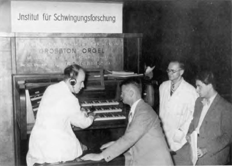 弗里茨·森海塞尔(坐者)与奥斯卡·威尔林在进阶力自欢电风琴旁,1935年赫兹研究所。