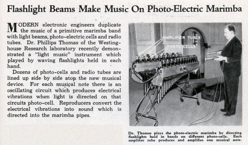 """光电马林巴的报道,标题为《使用光线创造音乐的光电马林巴琴》。正文:""""当代电子工程师使用光线、光电池以及电子管重制了一台古典马林巴琴。西屋实验室的菲利普·托马斯博士最近演示了一台'光电乐器',两只手各持一个手电筒,挥动双手,便可以进行演奏。这台乐器使用了许多光电池和电子管,这些部件一个挨一个、成排地安装在乐器上。每一个音符都有对应的振荡电路,当光束照射电路的光电装置时,振荡电路可以产生电振荡。声音再生器将电振荡转换为声音,直接导入到马林巴的声管中去。""""图注:托马斯博士正在使用手持的光源演奏光电马林巴琴;乐器中的每个放大管可以产生并放大一个音符。"""