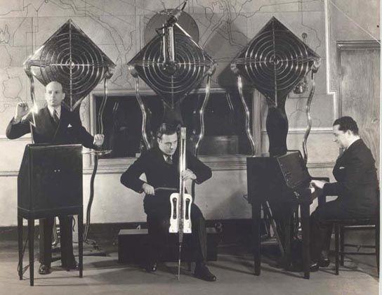 """""""泰勒明电子乐团""""组合,后来更名为""""电子乐团"""",摄于1932年。左一演奏RCA泰勒明琴的人,是泰勒明的助手朱丽叶斯·戈登堡(Julius Goldberg,这台泰勒明琴上装配有特制的装饰性铜镍合金天线,名为""""魔力闪电""""),中间演奏泰勒明大提琴的人是莱昂尼德·布鲁泰(Leonid Bolotine),右一正在演奏泰勒明键盘琴的是钢琴家格莱布·叶林(Gleb Yellin)。该乐团的音乐可在1932年每周一下午2:15时在哥伦比亚广播网(Columbia Network)的KMBC电台听到。[2]"""